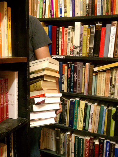 Man with Pile of Books in Bookshop